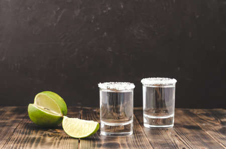 Tequila shot with lime slices and salt on wooden table/Tequila shots and lime slice on wooden table.With copy space on black background.