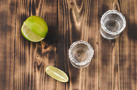 Tequila shots with lime slices and salt on wooden table/Tequila shots and lime slice on wooden table. Top view Foto de archivo