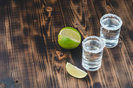 two Tequila shots with lime slices and salt on wooden table/Tequila shots and lime slice on wooden table with Copy cpace. Top view. Foto de archivo