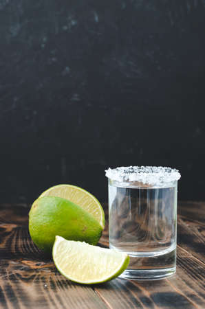 Tequila shot and lime slice on wooden table/Tequila shot and lime slice on wooden table. Dark background. Foto de archivo
