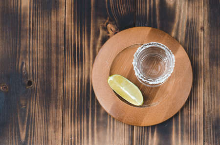 Tequila shot and lime slice on wooden table/Tequila shot and lime slice on wooden table with copy copyspace. Top view. Foto de archivo