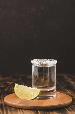 Tequila shot and lime slice on wooden table/Tequila shot and lime slice on wooden table. Dark background. Foto de archivo - 146816681