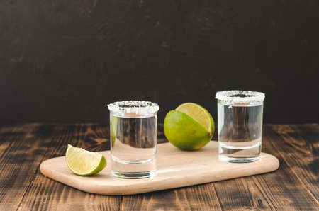 Tequila shot with lime slices and salt on wooden table/Tequila shots and lime slice on wooden table.With copy space on black background. Foto de archivo - 146816682