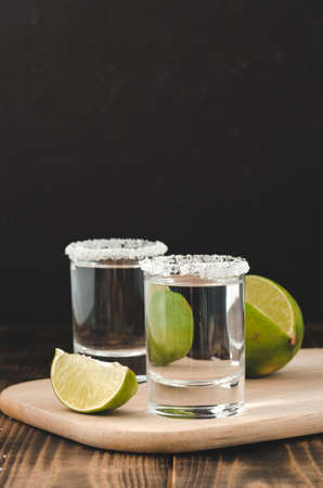 Tequila shot with lime slices and salt on wooden table/Tequila shots and lime slice on wooden table.With copy space on black background. Foto de archivo - 146816714