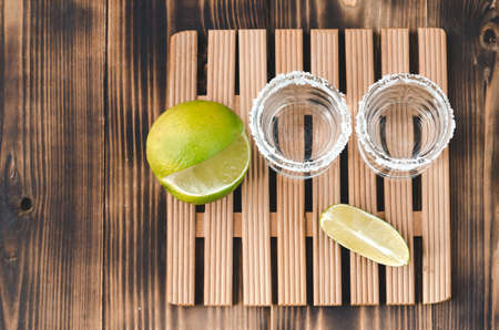 two Tequila shots with lime slices and salt on wooden table/Tequila shots and lime slice on wooden table with Copy cpace. Top view. Foto de archivo - 146816715
