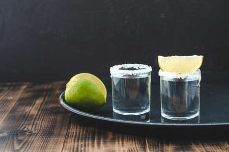 two Tequila shots with lime slices and salt on wooden table/Tequila shots and lime slice on wooden table with Copy cpace on dark background.