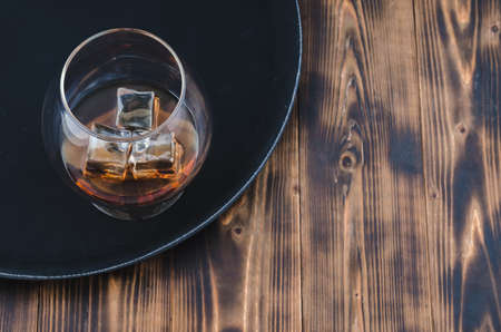 Glass of brandy with ice cubes/Glass of brandy with ice cubes on a black tray. Top view and copyspace.