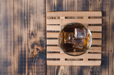 Glass of cognac with ice cubes on a wooden table/Glass of cognac with ice cubes on a wooden table. Top view, copyspace