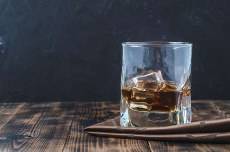 Glass of whiskey and ice cubes on a napkin/Glass of whiskey and ice cubes on a napkin, black background with copyspace. Wooden bar.