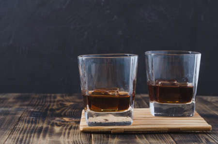 Two Glasses of whiskey with ice cubes on a wooden table/Two Glasses of whiskey with ice cubes on a wooden table. Black background with copyspace.