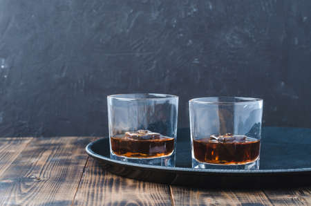 Glasses of whiskey with ice cubes on a black tray and wooden table/Two Glasses of whiskey with ice cubes on a black tray and wooden table. Black background with copyspace. Foto de archivo