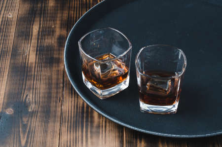 Glasses of whiskey with ice cubes on a black tray and wooden table/Two Glasses of whiskey with ice cubes on a black tray and wooden table with copyspace. Foto de archivo
