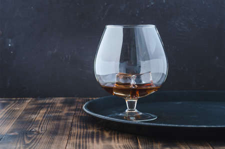 Glass of brandy with ice cubes/Glass of brandy with ice cubes on a black tray. Black background with copyspace.