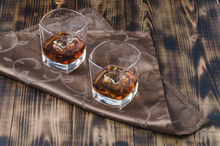 Two glasses of whiskey and ice cubes/Two glasses of whiskey and ice cubes on a napkin.