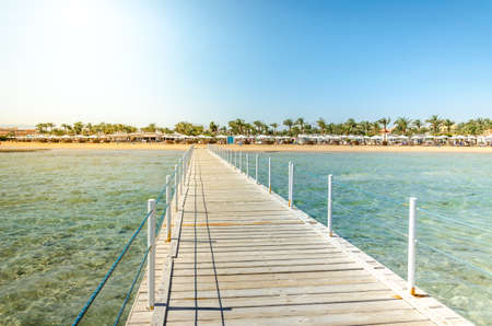 Wooden pier leading to the shore on a sunny day/beautiful wooden pier at the sea leading to the shore with blue sky