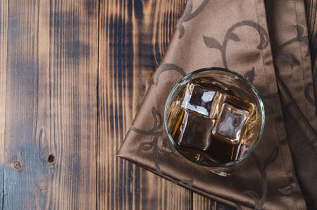 Glass of whiskey and ice cubes on a napkin/Glass of whiskey and ice cubes on a napkin. Wooden table with copyspace. Top view. Foto de archivo - 146816726