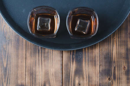 Glasses of whiskey with ice cubes on a black tray and wooden table/Two Glasses of whiskey with ice cubes on a black tray and wooden table with copyspace. Top view. Foto de archivo