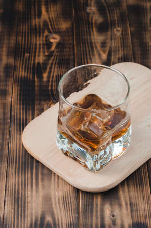 Glass of cognac with ice cubes on a wooden table/Glass of cognac with ice cubes on a wooden table. Top view.
