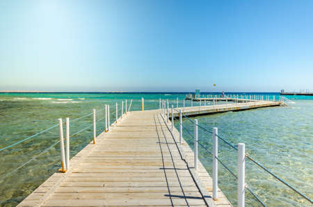Wooden pier leading to the sea on a sunny day/beautiful wooden pier leading to the sea with blue sky Foto de archivo