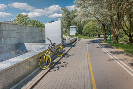 Bicycle parking near the bike path in the park/bikes parking on street in green park near lake Foto de archivo