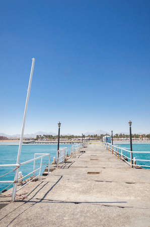 pier leading to the sea on a sunny day/empty pier overlooking the sea on a sunny day Foto de archivo