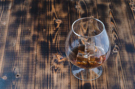 Glass of cognac with ice cubes on a wooden table/Glass of cognac with ice cubes on a wooden bar, copyspace. Beautiful glass. Foto de archivo
