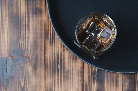 Glass of whiskey with ice cubes on a black tray and wooden table/Glass of whiskey with ice cubes on a black tray and wooden table. Top view and copyspace