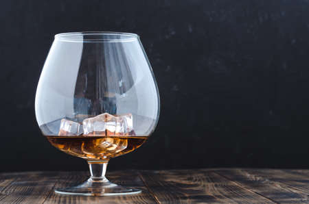 Glass of cognac with ice cubes on a wooden bar/Glass of cognac with ice cubes on a wooden bar. Black background with copyspace.