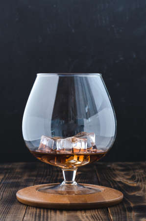 Glass of cognac with ice cubes on a wooden surface/Glass of cognac with ice cubes on a wooden surface. Selective focus