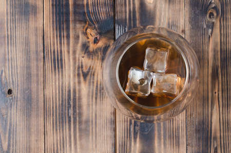 Glass of cognac with ice cubes on a wooden table/Glass of cognac with ice cubes on a wooden bar. Top view, copyspace