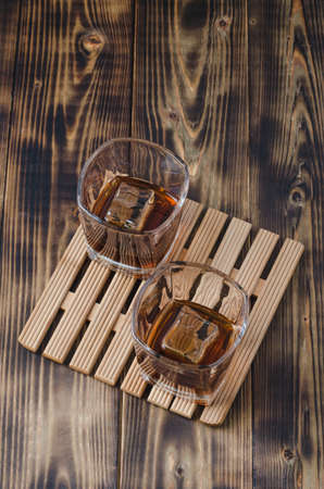Two Glasses of cognac with ice cubes on a wooden table/Two Glasses of cognac with ice cubes on a wooden table. Top view