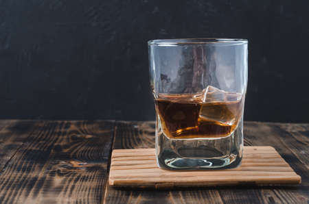Glass of cognac with ice cubes on a wooden bar/Glass of cognac with ice cubes on a wooden bar on the background with copyspace Foto de archivo