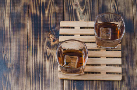 Two Glasses of whiskey with ice cubes on a wooden table/Two Glasses of cognac with ice cubes on a wooden table. Top view, copyspace