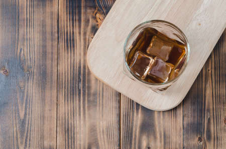Glass of cognac with ice cubes on a wooden table/Glass of cognac with ice cubes on a wooden table. Top view, copyspace Foto de archivo - 146562785
