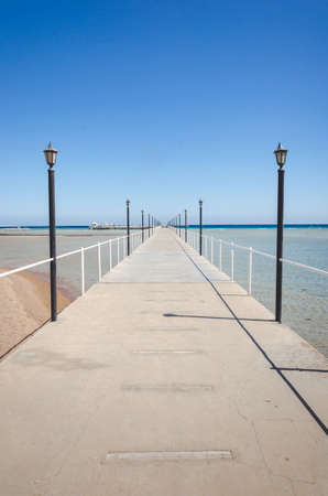 pier leading to the sea on a sunny day/empty pier overlooking the sea on a sunny day Foto de archivo - 146563083