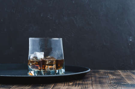 Glass of whiskey with ice cubes on a black tray and wooden table/Glass of whiskey with ice cubes on a black tray and wooden table. Black background with copyspace.