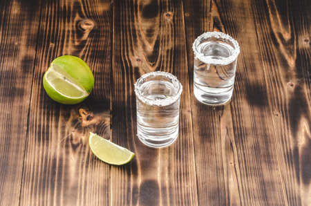Tequila shots with lime slices and salt on wooden table/Tequila shots and lime slice on wooden table