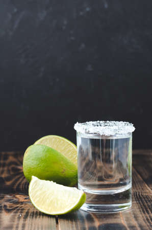 Tequila shot and lime slice on wooden table/Tequila shot and lime slice on wooden table with copy copyspace dark background