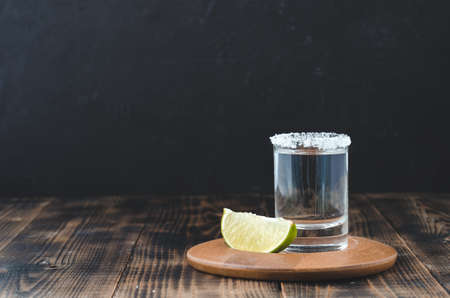 Tequila shot and lime slice on wooden table/Tequila shot and lime slice on wooden table with copy copyspace on dark background. Foto de archivo - 146816748