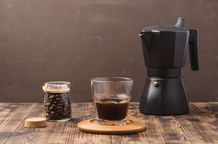 Glass of cofee with cofee beans and black maker. Selective focus. Cup of black coffee in a glass and grains in a glass jar with a coffee maker on a brown background.
