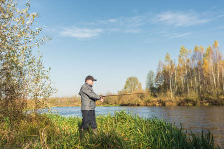Angler in a jacket with a fishing rod stands on the river bank. Fishing on the river