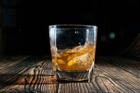 Whiskey with ice cubes on a wooden table. An old tabletop with light and a glass of strong drink. A splash of whiskey in a glass while serving ice.