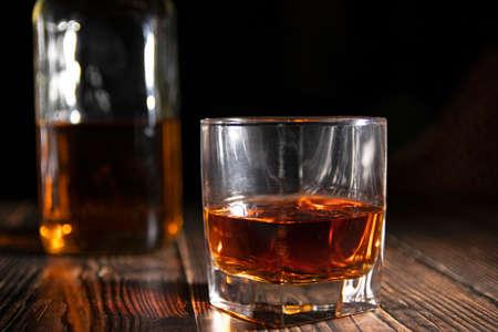 Glas Whisky mit Eiswürfeln, eine Flasche auf einem Holztisch. Eine alte Tischplatte mit Licht und einem Glas starkem Getränk.