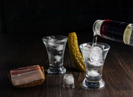 A bottle of vodka, two misted glasses of cold vodka with ice on a wooden board with bacon and pickles.