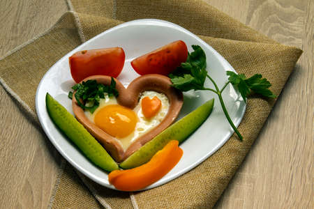 Creative breakfast. Fried eggs, sausages, toasts, tomatoes on a wooden table. Breakfast on Valentine's Day. Top view with copy space.