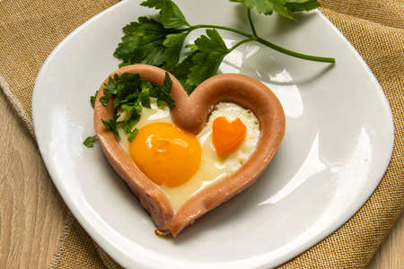 Creative breakfast with fried egg and sausages on a white plate on a wooden table, homemade continental breakfast in the home kitchen, morning breakfast for your beloved