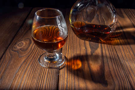 Pour cognac or brandy into a large glass on an old rustic table. Vintage wood background, night mood. Place for text, dark background, selective focus. Zdjęcie Seryjne