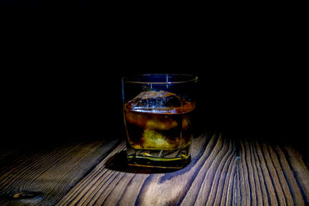 Whiskey with ice cubes on a wooden table made of dark wood on a dark background. Old table top with light and a glass of perfume. 免版税图像