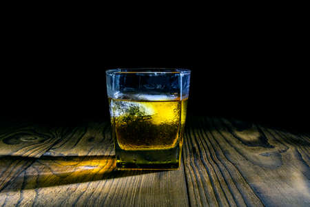 Whiskey with ice cubes on a wooden table made of dark wood on a dark background. Old table top with light and a glass of whiskey. 免版税图像