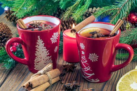 Two cups of aromatic hot mulled wine on a wooden table against the background of a Christmas tree with lights. Festive atmosphere concept.